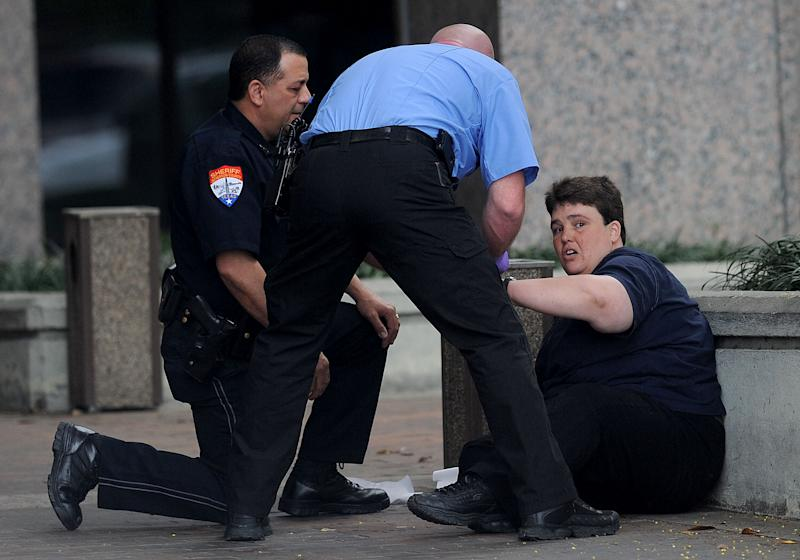 A victim who was wounded in the hand during a shooting at the Jefferson County Courthouse Wednesday, March 14, 2012 is assisted by a deputy and a paramedic in Beaumont, Texas. Bartholomew Granger open fired wounding several and killing one. (AP Photo/The Beaumont Enterprise, Guiseppe Barranco)