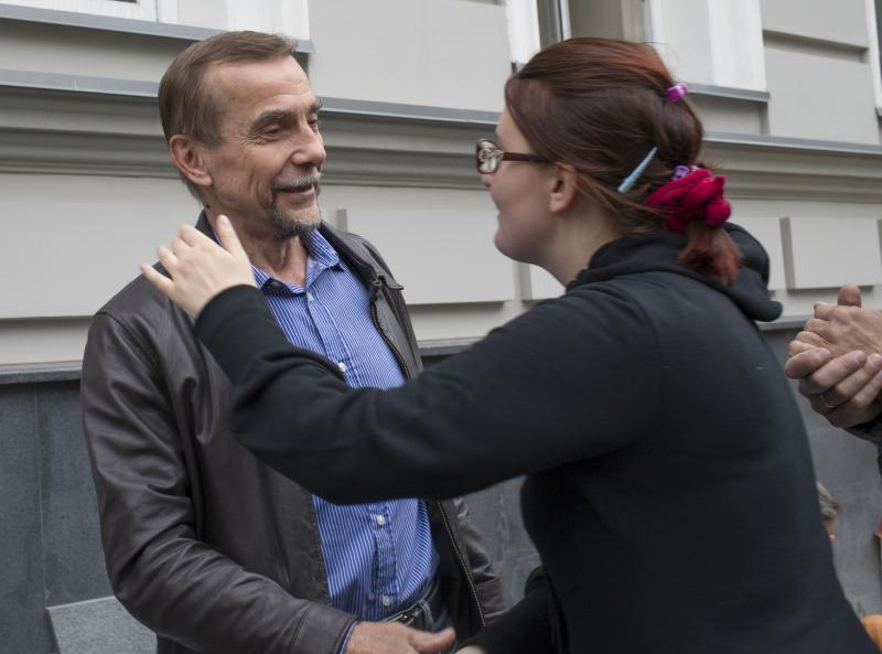 Russian human rights activist Lev Ponomarev, left, is greeted by his supporter at the For Human Rights movement headquarters in Moscow, Russia, Saturday, June 22, 2013. Law enforcement officers forcibly evicted the head of one of Russia's leading human rights groups and about a half dozen staff from their Moscow office early Saturday, in the latest in a series of attacks on Russian non-governmental organizations. Lev Ponomaryov, 72, who heads For Human Rights, said he was beaten all over his body when officers stormed the building at around 3 a.m. and dragged him out. Dozens of riot police had raided the office on Friday and ordered employees to leave, but they had refused. (AP Photo/Alexander Zemlianichenko)