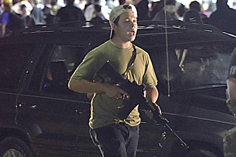 Kyle Rittenhouse carries a weapon as he walks along Sheridan Road in Kenosha, Wis., on Aug. 25, 2020. (Adam Rogan / AP file)