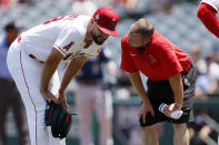 Los Angeles Angels starting pitcher Patrick Sandoval, left, talks to trainer Brian Reinker on the mound after a comebacker hit by Seattle Mariners' Ty France hit Sandoval during the first inning of a baseball game in Anaheim, Calif., Sunday, July 18, 2021. Sandoval continued to pitch in the inning. (AP Photo/Alex Gallardo)