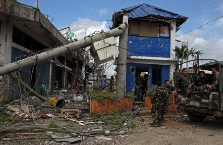 Soldiers stand on guard in front of damaged buildings after government troops cleared the area from pro-Islamic State militant groups inside a war-torn area in Bangolo town, Marawi City, southern Philippines October 23, 2017. REUTERS/Romeo Ranoco