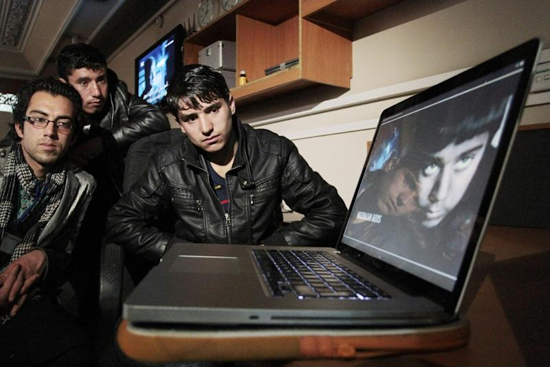 """Ahmad Jawad Mohammadi, 19, right, and Ahmad Jawed Mohammadi, 15, center, brothers of Fawad Mohammadi, 14, the Afghan star of the Oscar-nominated movie """"Buzkashi Boys,"""" join their brother-in-law Mohammad Fahim Naderi, 20, left, as they watch an announcement of the Oscar results in Kabul, Afghanistan, early Monday, Feb. 25, 2013. Relatives of the young Afghan star of the Oscar-nominated movie """"Buzkashi Boys"""" expressed more pride than disappointment upon learning on Monday that the movie didn't win. (AP Photo/Musadeq Sadeq)"""