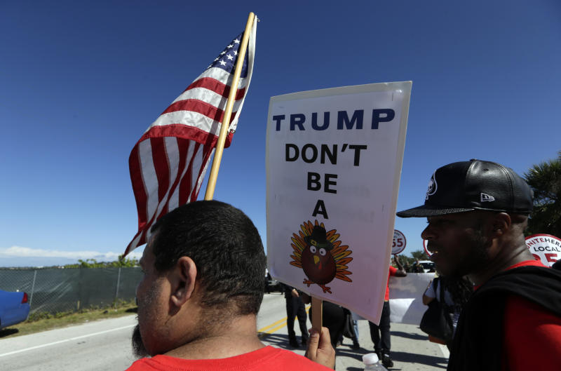 Protesters march to President Donald Trump's Mar-a-Lago resort, where he will be spending the Thanksgiving holiday, Tuesday, Nov. 21, 2017, in West Palm Beach, Fla. They were protesting the Trump administration's decision to end a temporary residency permit that has allowed almost 60,000 citizens from Haiti to live and work in the United States since an earthquake shook the Caribbean nation in 2010. (AP Photo/Lynne Sladky)