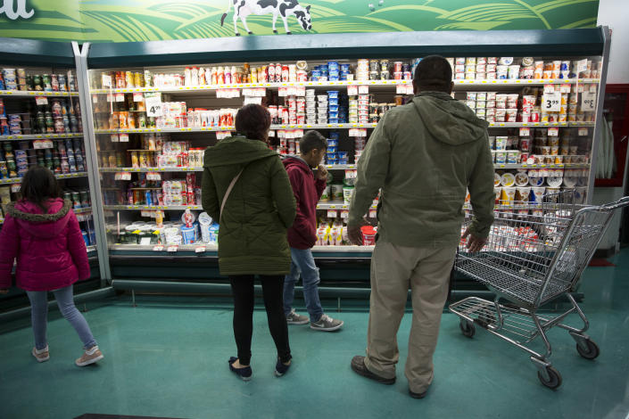 Lorena and her children shop at the grocery store in Juarez with Alex Varela on Nov. 28, to buy food for the temporary home they are staying at until their numbers are up on the waiting list. (Photo: Adria Malcolm for Yahoo News)