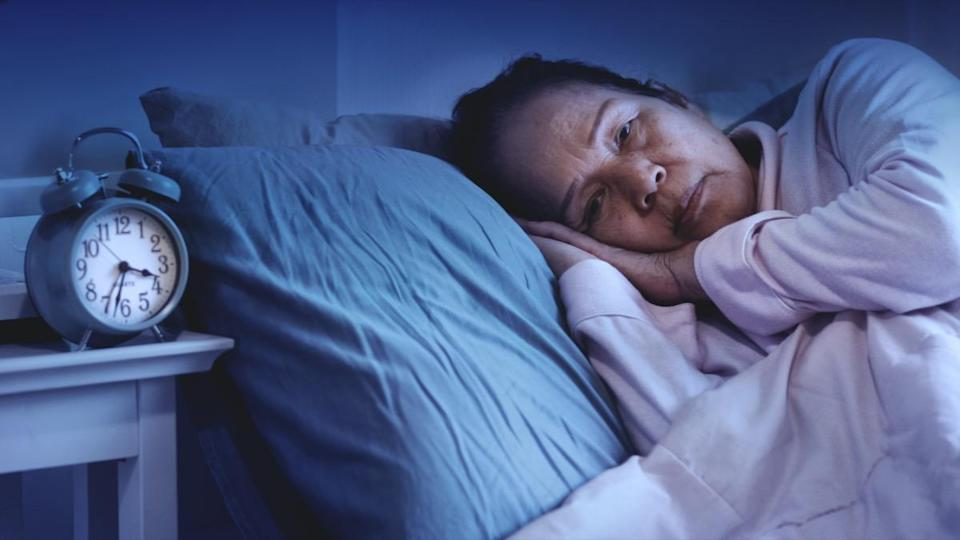senior woman having sleep disorder, sitting in bed look sad