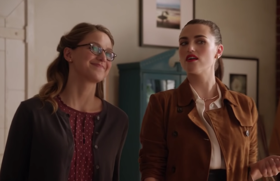 Kara Danvers, wearing a red polka dot shirt under a brown cardigan, smiles as Lena Luthor, wearing a white blouse under a brown jacket, has a skeptical look on her face