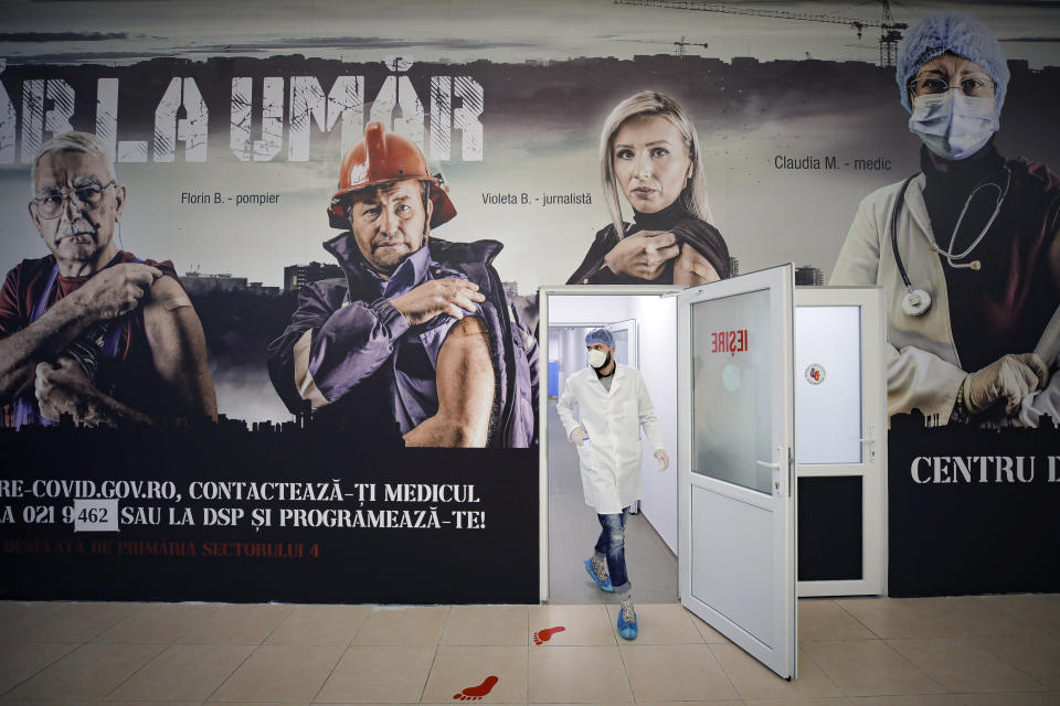 A member of the medical staff walks under a mural advertising the COVID-19 vaccination campaign at a vaccination center that offers both AstraZeneca and Pfizer vaccines in Bucharest, Romania, Tuesday, March 23, 2021. (AP Photo/Vadim Ghirda)