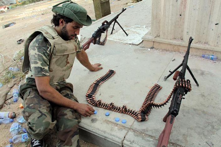 A man, wearing military fatigues, sits next to weapons and ammunition during fightings between rival militias around Tripoli international airport, on August 17, 2014 (AFP Photo/Mahmud Turkia)