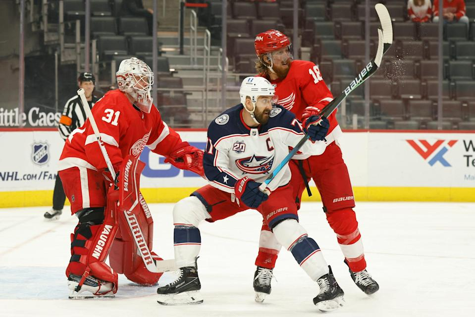 Columbus Blue Jackets left wing Nick Foligno (71) and Detroit Red Wings defenseman Marc Staal (18) fight for position with in front of goaltender Calvin Pickard (31) in the first period on March 27, 2021, at Little Caesars Arena in Detroit.