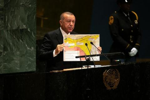 """Recep Tayyip Erdogan, Turkey's president, holds up a map of his proposed """"safe zone"""" while speaking during the UN General Assembly meeting in New York - Credit: Bloomberg"""