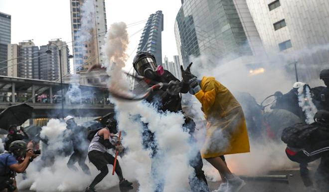 A protester uses a tennis racket to hit a ear gas canister back at police on August 25 during a clash in Tsuen Wan. Photo: Sam Tsang