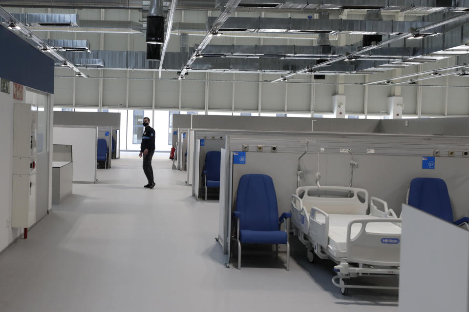 A security guard walks in the empty Isabel Zendal new hospital during the official opening in Madrid, Spain, Tuesday, Dec. 1, 2020. Authorities in Madrid are holding a ceremony to open part of a 1,000-bed hospital for emergencies that critics say is no more than a vanity project, a building with beds not ready to receive patients and unnecessary now that contagion and hospitalizations are waning. Spain has officially logged 1.6 million infections and over 45,000 deaths confirmed for COVID-19 since the beginning of the year. (AP Photo/Paul White)