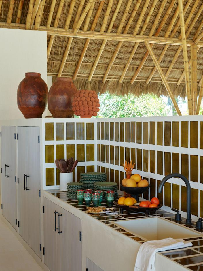 Custom tiles by Cerámica Suro line a kitchen sink at one end of the palapa living room. Tableware by Perla Valtierra; vases by Arte Ananås.