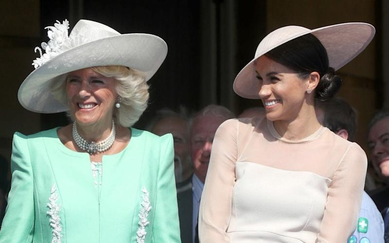 The Duchess of Sussex shares a joke with the Duchess of Cornwall at a Buckingham Palace garden party - Getty Images Europe