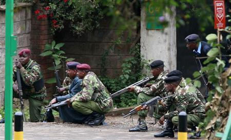 Kenyan police officers take position during the ongoing military operation at the Westgate Shopping Centre in the capital Nairobi, September 23, 2013. Gunfire and explosions sounded on Monday from the Nairobi mall where militants from Somalia's al Qaeda-linked al Shabaab group threatened to kill hostages on the third day of a raid in which at least 68 have already died. REUTERS/Thomas Mukoya