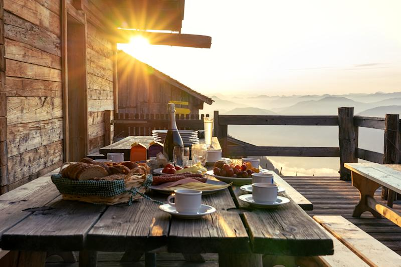 Breakfast table in rustic wooden terace patio of a hut hutte in Tirol alm at sunrise .