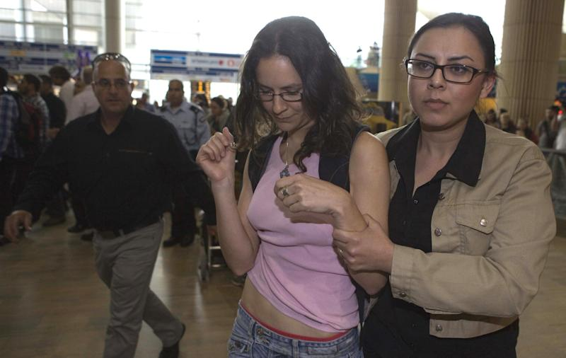"""An Israeli left-wing activists is detained at Ben Gurion Airport near Tel Aviv, Israel, Sunday, April 15, 2012. Four Israeli were arrested for causing a disturbance at the main airport terminal after unfurling a banner bearing the theme of the protest, """"Welcome to Palestine,"""" a police spokesman said. Israel deployed hundreds of police Sunday at its main airport to detain activists flying in to protest the country's occupation of Palestinian areas, defying vigorous Israeli government efforts to block their arrival. (AP Photo/Dan Balilty)"""