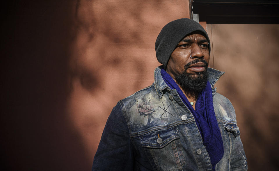 "Painter Guy Stanley Philoche, a 43-year-old Haitian immigrant and star in the New York art world, pose outside his East Harlem studio, Thursday Nov. 19, 2020, in New York. After a hugely successful gallery show, Philoche wanted to treat himself to a fancy $15,000 watch, instead he bought the works of fellow artists struggling in the pandemic. ""I'm not a rich man,"" he said, ""but I owe a big debt to the art world."" (AP Photo/Bebeto Matthews)"