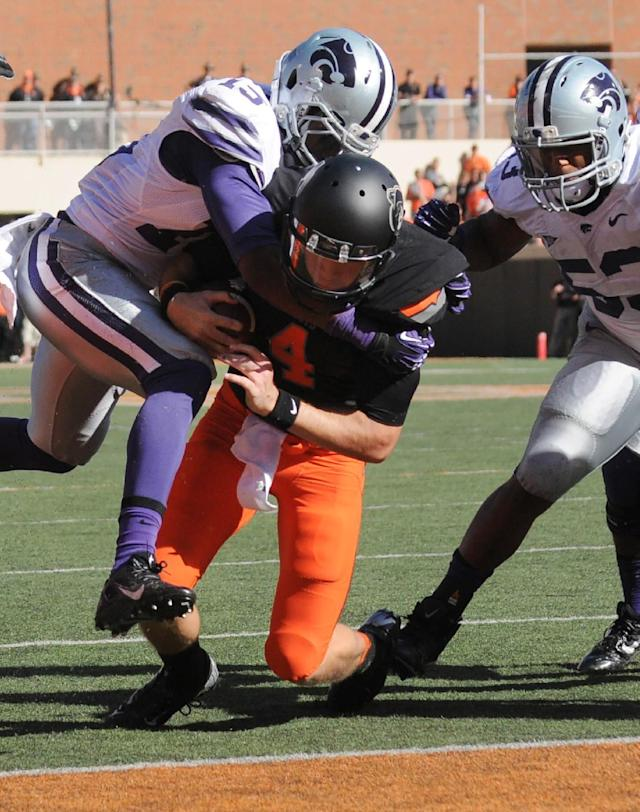 Kansas State teammates Randall Evans, left, and Blake Slaughter, right, attempt to stop Oklahoma State quarterback J.W. Walsh, as he scores a touchdown during the first half of an NCAA football game in Stillwater, Okla., Saturday, Oct. 5, 2013. Oklahoma State won 33-29. (AP Photo/Brody Schmidt)