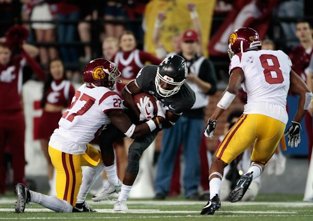 "PULLMAN, WA – SEPTEMBER 29: Renard Bell #81 of the Washington State Cougars carries the ball against Aiene Harris #27 and <a class=""link rapid-noclick-resp"" href=""/ncaaf/players/255263/"" data-ylk=""slk:Iman Marshall"">Iman Marshall</a> #8 of the <a class=""link rapid-noclick-resp"" href=""/ncaab/teams/uad/"" data-ylk=""slk:USC Trojans"">USC Trojans</a> in the first half at Martin Stadium on September 29, 2017 in Pullman, Washington. (Photo by William Mancebo/Getty Images)"