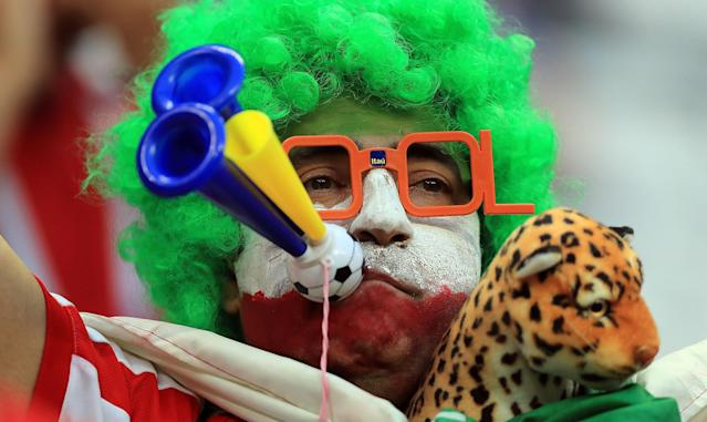 <p>An Iranian fan goes all out with a wig, face paint, accessories and a cuddly toy in his effort to impress. (Getty) </p>