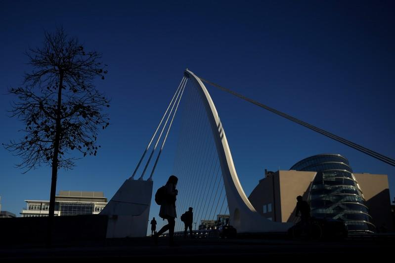 Commuters walk into work in the morning in the financial district of Dublin