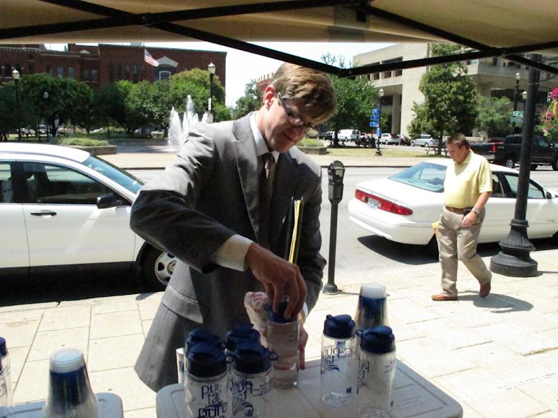 Nick Neumann puts the lid on a bottle of water drawn from the tap on Thursday, June 28, 2012, in Louisville, Ky., during a midday break. The free water was offered by Louisville Water Co. to help people keep hydrated as temperatures soared. (AP Photo/Bruce Schreiner)