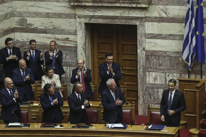 Greece's Prime Minister Kyriakos Mitsotakis, right, is applauded by lawmakers after presenting his government's policies during a parliamentary session in Athens, Saturday, July 20, 2019.(AP Photo/Petros Giannakouris)