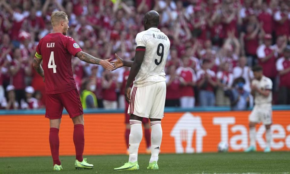 Denmark captain Simon Kjær shakes hands with Belgium's Romelu Lukaku as the players stop play after 10 minutes in tribute to Christian Eriksen.