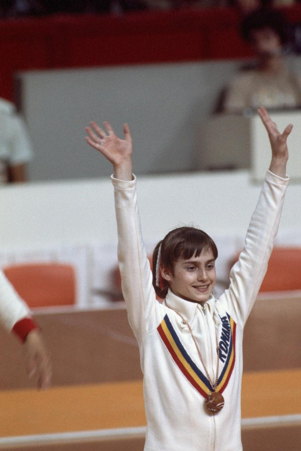 <p>Nadia Comăneci, the first Olympic gymnast to score a perfect 10, didn't just wear one medal during the 1976 Olympic games, but this one allowed her to show off her Romania sports jacket that matched the same Adidas crafted bodysuit she wore for that iconic moment, along with the ribbon in her hair. She received a total of <i>six</i> more perfect 10s during events leading up to her three gold medals that year.</p>
