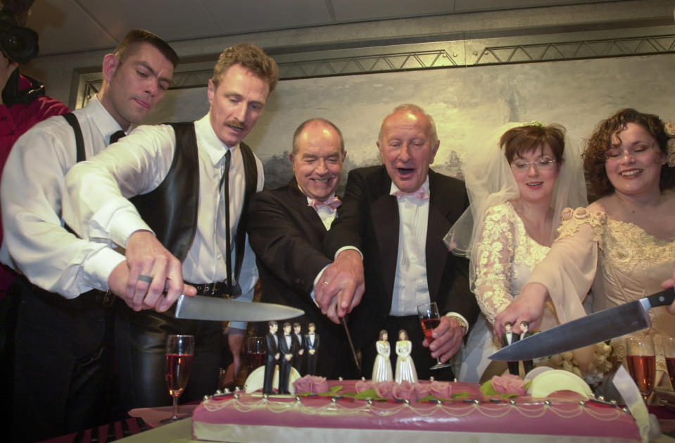 Peter Wittebrood-Lemke, from left, Frank Wittebrood, Ton Jansen, Louis Rogmans, Helene Faasen and Anne-Marie Thus cut the wedding cake after exchanging vows at Amsterdam's City Hall early Sunday, April 1, 2001. The pairs were among four couples to get married under a new law which took effect April 1, 2001, the world's first such law allowing same-sex marriages with equal rights. (AP Photo/Peter Dejong)