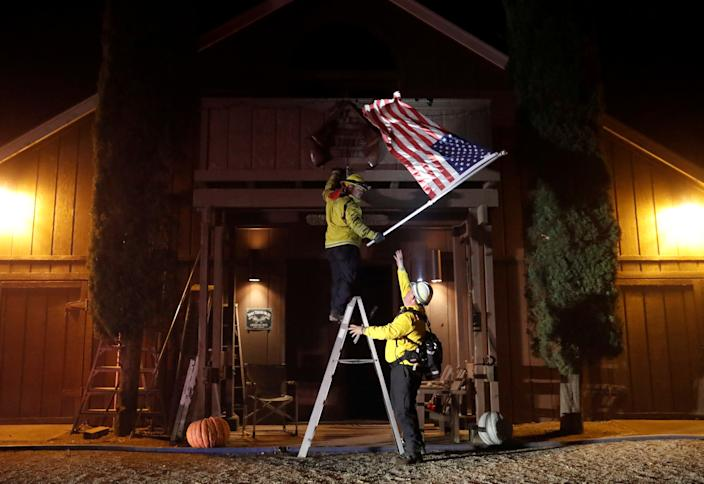 Firefighters remove a flag off a barn, as the wind driven Kincade fire burns near the town of Healdsburg, California, Oct. 27, 2019. (Photo: Stephen Lam/Reuters)
