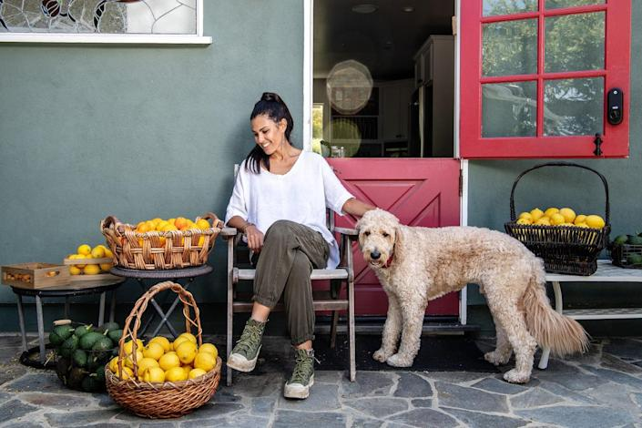Alexandra Dorros with her dog and baskets of fruit