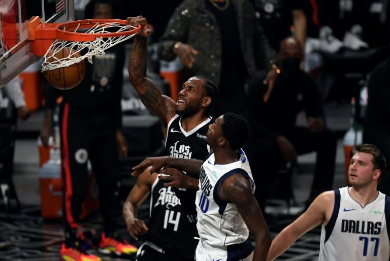 Los Angeles Clippers Kawhi Leonard, left, dunks the ball against Dorian Finney-Smith, center, of the Dallas Mavericks during the first half of game seven of the Western Conference first round series at Staples Center