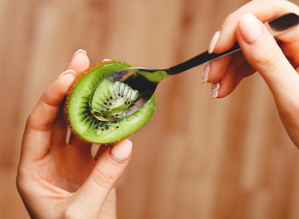 Woman using spoon to eat kiwi