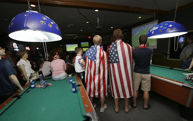 Fans draped in flags watch the World Cup Soccer match between the United States and Germany at a local bar, Thursday, June 26, 2014, in West Des Moines, Iowa. Thousands of eager Americans set work aside on Thursday _ with or without their bosses' OK _ to watch the key World Cup match. (AP Photo/Charlie Neibergall)