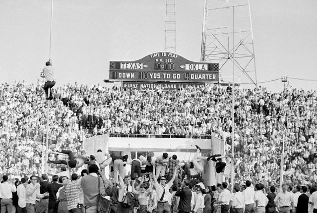 FILE - In this Oct. 8, 1966, file photo, joyous Oklahoma Sooner fans climb the goal posts to tear down the cross bar after Oklahoma defeated Texas 18-9 in a college football game at the Cotton Bowl in Dallas. No. 5 Oklahoma and No. 9 Texas are playing in a rare Red River rivalry rematch in the Big 12 championship game on Saturday. It is the first time in 115 years that the border state rivals will play twice in the same season. (AP Photo/Ferd Kaufman, File)