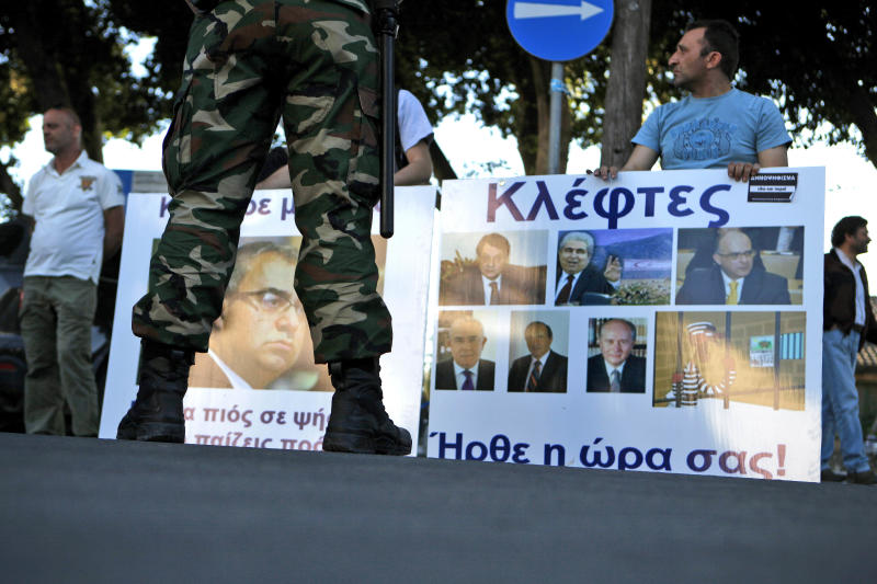 A riot police stands in front of protestors,  with a banner display the image of the head of Cyprus central bank Panicos Dimitriades,  and right, a banner displaying the image the president Nicos Anastasiades,  former president Dimitris Christofias, and other members of parliament, during an anti-bailout protest outside of the Cyprus' parliament in capital Nicosia, Thursday, April 25, 2013. Cyprus' central bank says the Romanian operations of the island nation's largest lender Bank of Cyprus will resume April 26th after being suspended for more than three weeks amid plans to sell them off. (AP Photo/Petros Karadjias)