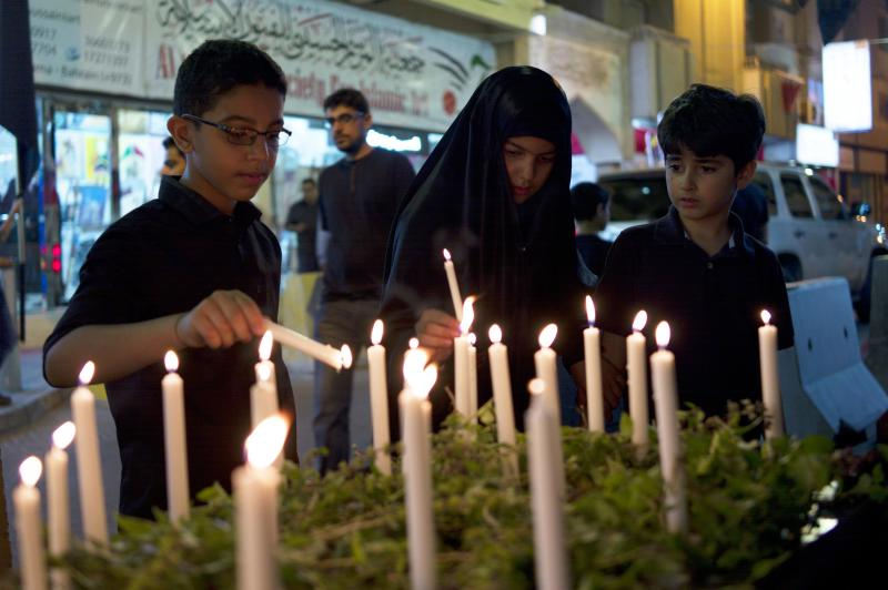 Youths light candles at a candlelight vigil to show their solidarity with victims of Super Typhoon Haiyan, in Manama