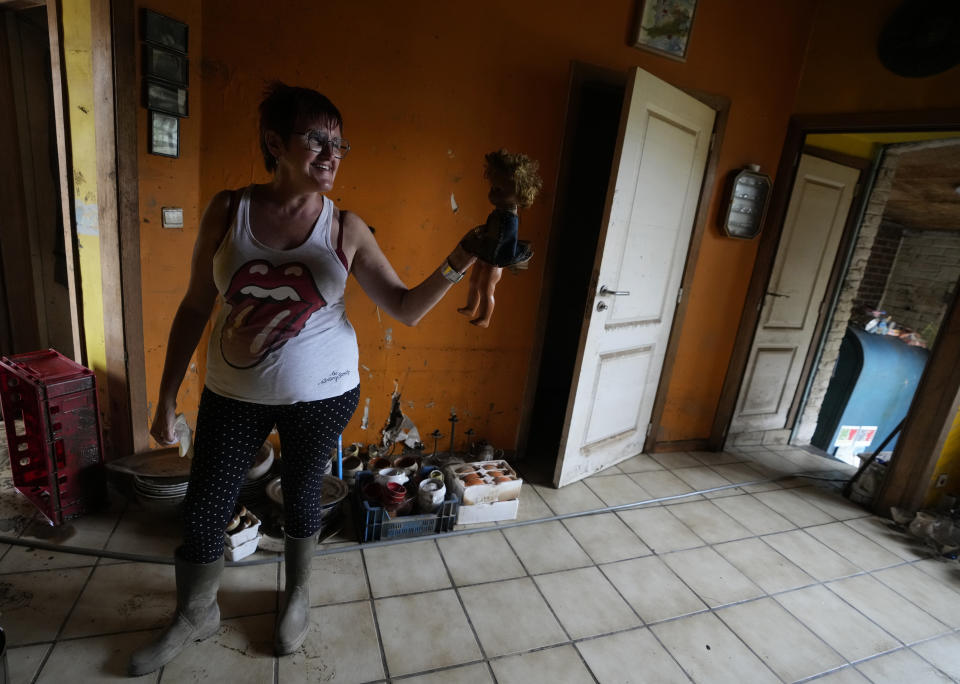 Resident Carine Lacroix holds up a doll she rescued from her flood damaged home in the La Brouck neighborhood of Trooz, Belgium, Tuesday, July 27, 2021. Lacroix and her companion still find it hard to sleep after they feared for their lives during deadly floods nearly two weeks ago, isolated and trapped in the top floor of their house for two days before they were rescued on a small boat by firefighters. (AP Photo/Virginia Mayo)