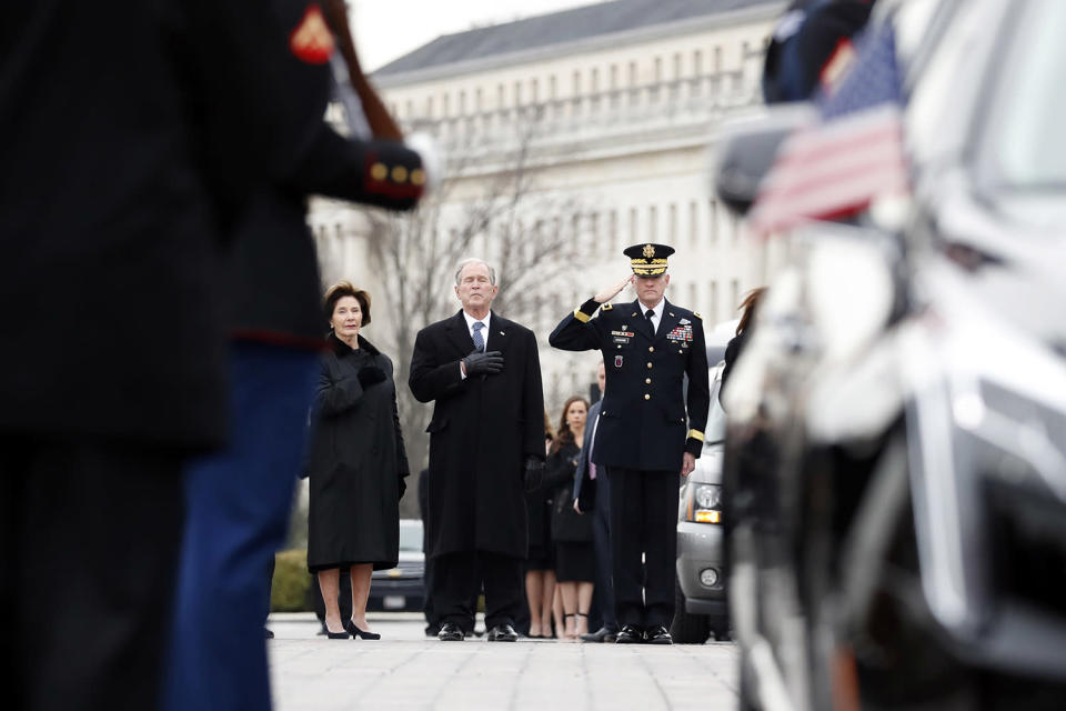Former President George W. Bush and former first lady Laura Bush put their hands over their hearts as a joint services military honor guard carries the flag-draped casket of former President George H. W. Bush from the U.S. Capitol to transport it to Washington National Cathedral, Dec. 5, 2018 in Washington, D.C. (Photo: Alex Brandon – Pool/Getty Images)
