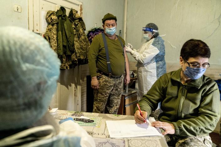 A Ukrainian serviceman receives a dose of the AstraZeneca COVID-19 vaccine marketed under the name CoviShield at a military base near the front-line town of Krasnohorivka, eastern Ukraine, Friday, March 5, 2021. The country designated 14,000 doses of its first vaccine shipment for the military, especially those fighting Russia-backed separatists in the east. Ukrainians are becoming increasingly opposed to vaccination: an opinion poll this month by the Kyiv International Institute of Sociology found 60% of the country's people don't want to get vaccinated, up from 40% a month earlier. (AP Photo/Evgeniy Maloletka)