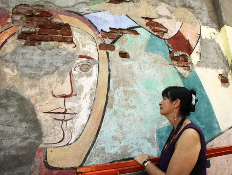 """In this Sept. 13, 2011 photo, elevated by a scissor-lift, Arnold Belkin's widow Patricia Quijano Ferrer studies damage to a detail of Belkin's 1972 public mural """"Against Domestic Colonialism,"""" which adorns the wall of a Hell's Kitchen community playground in New York. Against Domestic Colonialism"""" in 1972.  The national organization Heritage Preservation has called it one of the most endangered public murals in the country. (AP Photo/Kathy Willens)"""
