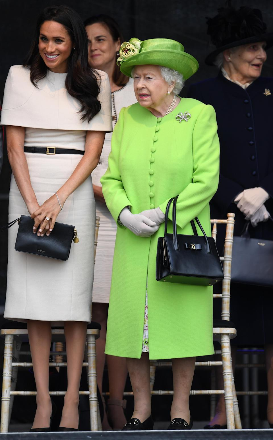 <p>For Meghan Markle's debut solo engagement with Queen Elizabeth II on 14 June, she chose a Givenchy cape-dress. The former 'Suits' star accessorised the look with a black clutch and co-ordinating heels by American designer Sarah Flint. The Queen on the other hand dazzled in a lime green coat and spring-ready floral dress. <em>[Photo: Getty]</em> </p>