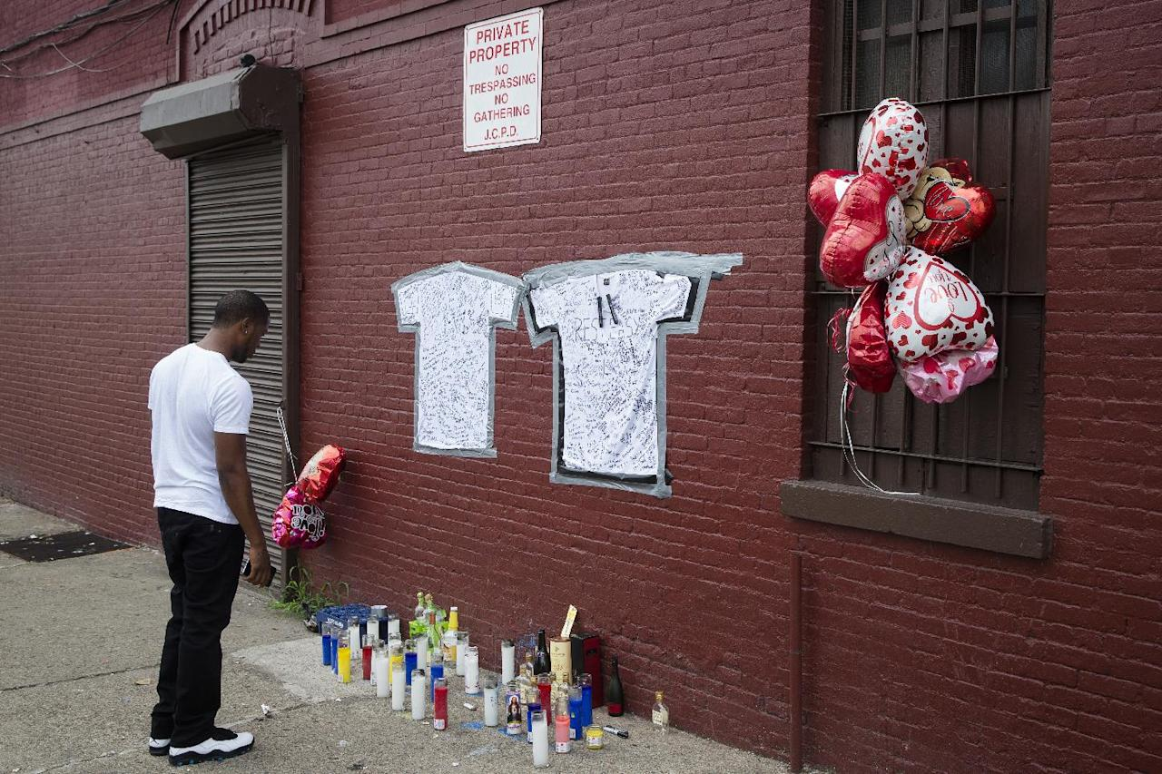 A pedestrian stands at a memorial to Lawrence Campbell, who allegedly shot and killed 23-year-old Jersey City police officer Melvin Santiago, Monday, July 14, 2014, in Jersey City, N.J. Campbell was also killed at the scene after police officers returned fire. (AP Photo/John Minchillo)