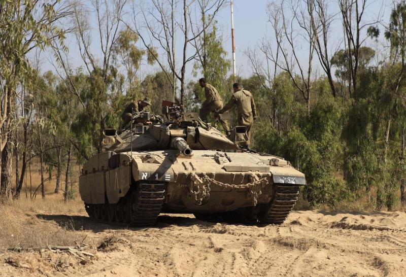 Israeli soldiers man a tank position at the border with Gazar in southern Israel, Friday, June 1 2012. An Israeli soldier and a Palestinian militant died in a shootout between the militant and Israeli troops near the border with the Gaza Strip early Friday, the military said. The exchange of fire began after the militant crossed the fence separating the Hamas-run coastal strip and southern Israel. (AP Photo / Tsafrir Abayov)