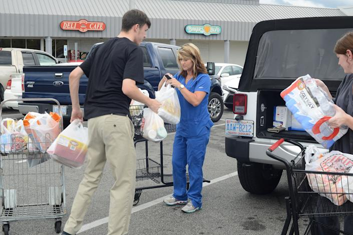 From left, Douglas Hill loads groceries into Wendy Cannon's jeep as she and Logan Coombs, right, purchased items from the Piggly Wiggly in preparation for Hurricane Florence in Kinston, North Carolina, on Monday.