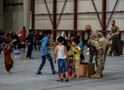 US military personnel are seen handing out sweets to Afghan evacuee children at Al-Udeid air base in Qatar, in an image released by US Central Command
