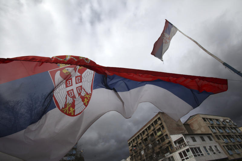 In this photo taken Friday, March 29, 2013, Serbian flags fly over a barricade in front of the main bridge, one of two bridges between the southern, ethnic Albanian-dominated and northern, Serb-dominated part of Mitrovica, Kosovo. Mitrovica, a former mining center in northern Kosovo, was sharply split into Serb and Albanian parts at the end of the Kosovo war in 1999. The town's fate has come into renewed focus as officials from Serbia and Kosovo meet in Brussels on Tuesday in hopes of reaching an agreement that could pave the way for reuniting the divided city. (AP Photo/Darko Vojinovic)