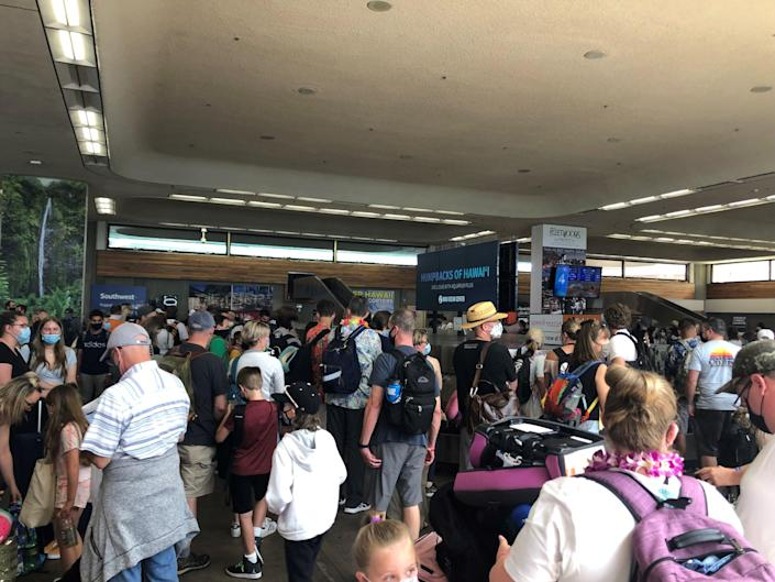 Passengers arriving in Maui wait for bags in the cramped baggage claim area of Kahului Airport. Hawaii has recently reduced its restaurant and bar capacity to stem the spread of COVID-19.